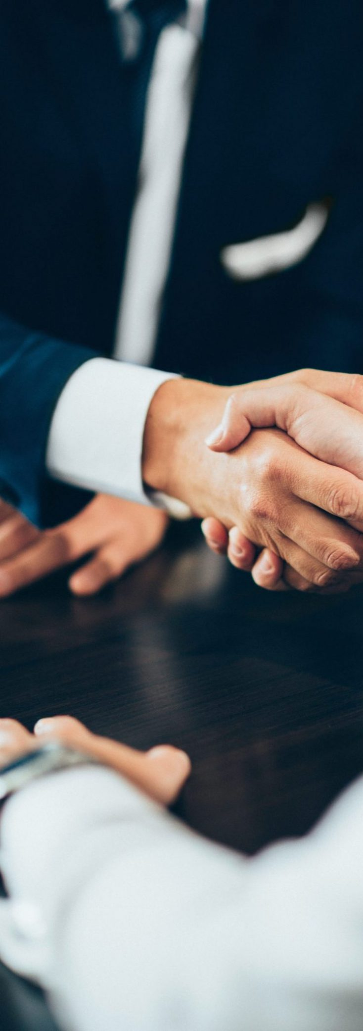 Business people reaching agreement, shaking hands. Toned image, focus on handsake